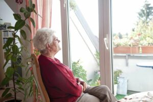 Senior woman in isolation at home looking outside her backyard window.